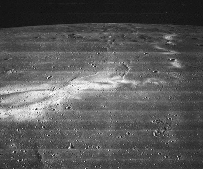 A bright feature known as Reiner Gamma snakes across the lunar surface in this 1967 image from Lunar Orbiter 2. It is one of several features known as lunar swirls. They are thin layers of material that often form swirls or squiggles. Planetary scientists are still trying to understand their origin. [NASA]