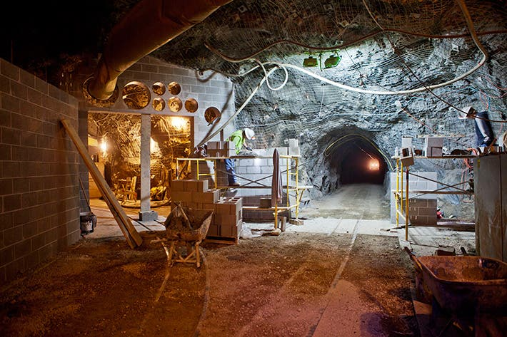 The Large Underground Xenon (LUX) Dark Matter Detector  is located 4,850 ft (about 1 mile) underground at the Sanford Underground Laboratory in the Homestake Mine in Lead, South Dakota. The LUX experiment needs to be operated underground in order to reduce signal background caused by high-energy cosmic rays at the Earth's surface. Construction workers turned this former gold mine into a state-of-the-art underground research facility. The tunnel to the right, shown at the time of construction, provides access to the cavern that houses the LUX experiment. (Image Credit: Matt Kapust, Sanford Underground Research Facility)