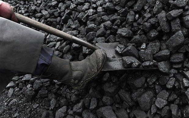 A coal merchant shovels coal at a coal yard in Melmerby, northern England. Photo: Telegraph