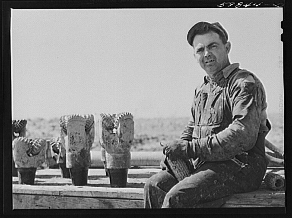 "Jim Eckles, water pumper, ""backup man,"" with drill bits used in oil well in C.C. Graber pool, Continental oil company. Moundridge area near McPherson, Kansas"