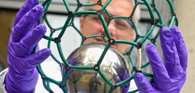 Scientist holds model of N@C60 ( The @ (at sign) in the name reflects the notion of a small molecule trapped inside a shell). Image: Oxford University