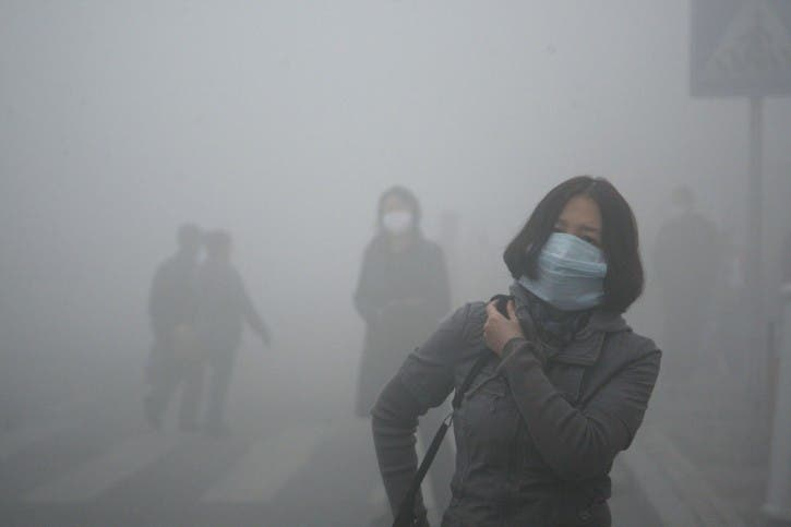 A woman wearing a mask walk through a street covered by dense smog in Harbin, northern China, Monday, Oct. 21, 2013. Visibility shrank to less than half a football field and small-particle pollution soared to a record 40 times higher than an international safety standard in one northern Chinese city as the region entered its high-smog season. (AP Photo/Kyodo News)