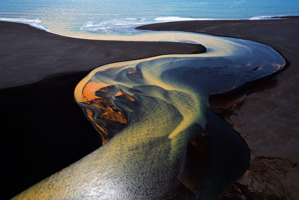 One of a series of aerial shots taken from a helicopter over the fabulous river deltas in South Iceland.  This one depicts one river winding its way to the ocean.  The brilliant colors are a result of mineral deposits picked up by the glacial waters as they flow towards the sea. We were lucky to shoot on a gorgeously sunny day