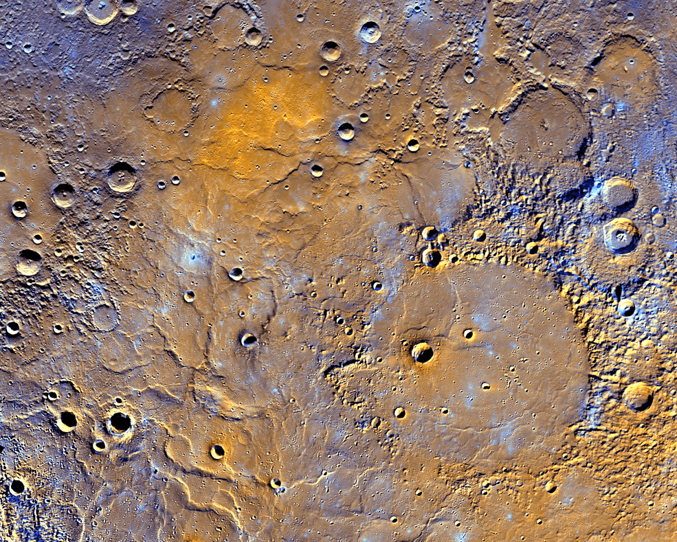 A view of Mercury's northern volcanic plains is shown in enhanced color to emphasize different types of rocks on Mercury's surface. In the bottom right portion of the image, the 181-mile- (291-kilometer)-diameter Mendelssohn impact basin, named after the German composer, appears to have been once nearly filled with lava. Toward the bottom left portion of the image, large wrinkle ridges, formed during lava cooling, are visible. Also in this region, the circular rims of impact craters buried by the lava can be identified. Near the top of the image, the bright orange region shows the location of a volcanic vent. Credits: NASA/JHUAPL/Carnegie Institution of Washington