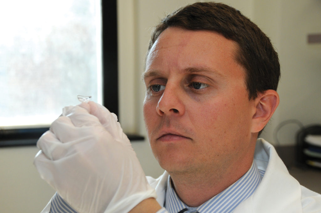 Dr. Ciolino holding the medicine dispensing contact lens he and colleagues made. Credit: John Earle Photography