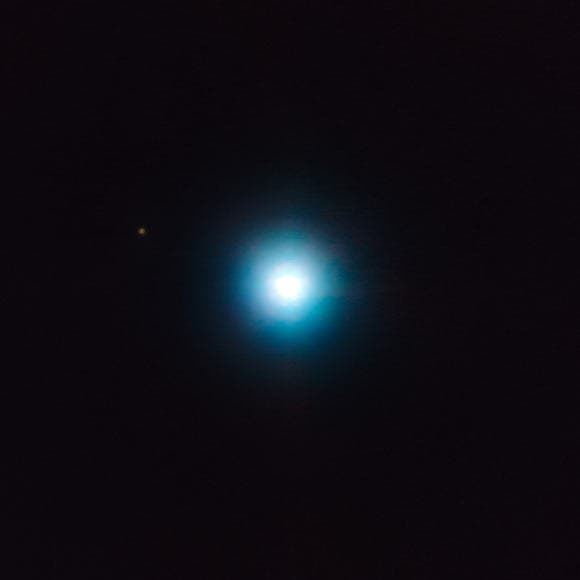The small dot on the upper left is CVSO 30c. The large white blob is the planet's parent star, CVSO 30. Credit: ESO