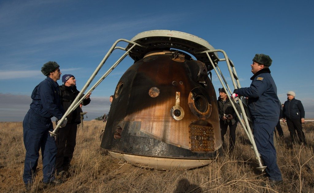 A battered Soyuz craft from the atmospheric re-entry with the crew still inside, shortly before the hatch was opened and the astronauts touched Earth for the first time in 115 days. Credit: Bill Ingalls/NASA