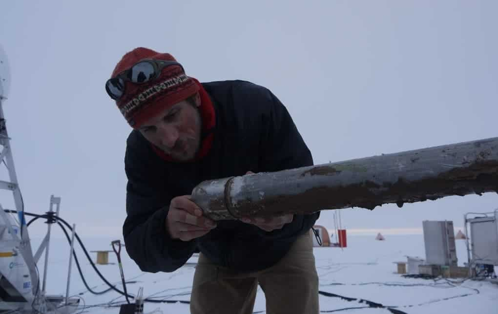 A researcher inspecting a sediment core drilling from 1,000 feet beneath the Pine Island Glacier ice shelf. Credit: M. Brian/Nature