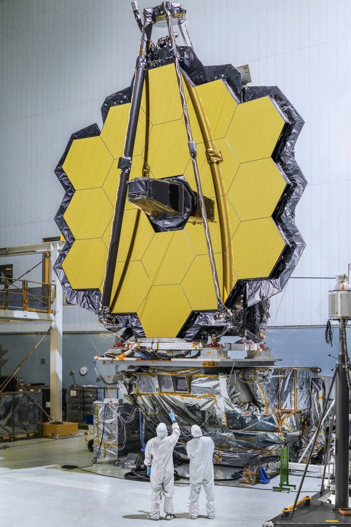 The primary mirror of NASA's James Webb Space Telescope consisting of 18 hexagonal mirrors looks like a giant puzzle piece standing in the massive clean room of NASA's Goddard Space Flight Center in Greenbelt, Maryland. Credit: NASA