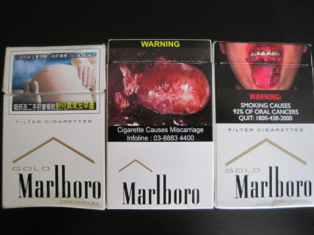 Cigarette boxes from Taiwan (far left), Malaysia (center), and Singapore (far right). Guidelines for pictorial warnings vary considerably from country to country. Credit: Justin Calderon