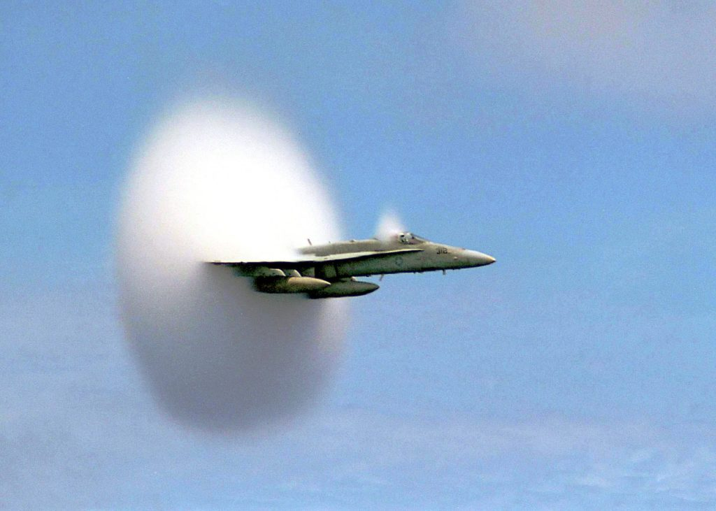 A fighter jet photographed in the midst of a sonic boom. The plane travels faster than the sound it emits. As it pieces the sound wave, a roaring boom commences. Credit: YouTube capture.
