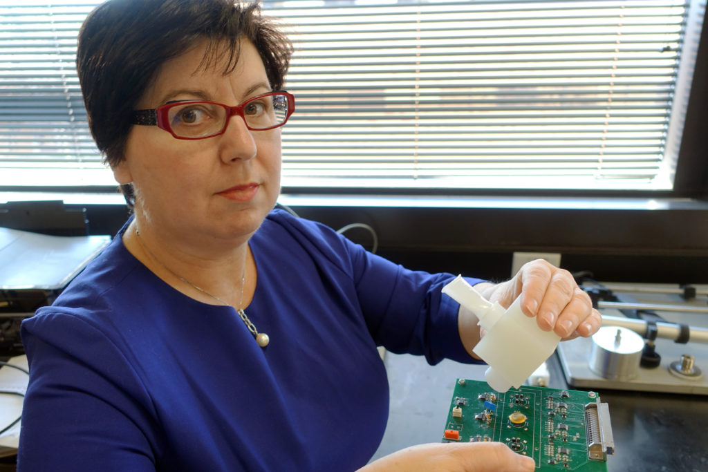 Perena Gouma pictured with her invention -- a hand-held breath monitor that can detect the flu virus. Credit: UT Arlington