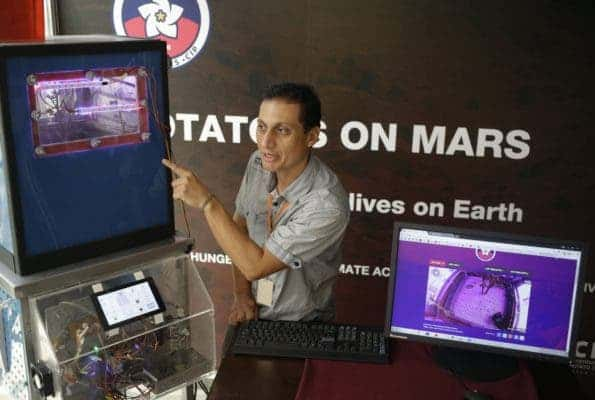Peruvian scientist David Ramirez points to a potato plant in a simulator akin to a Mars' conditions, in Lima Peru.