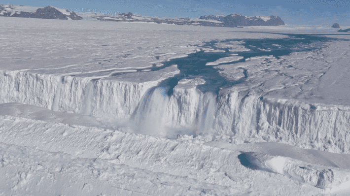 An enormous waterfall gushes off the Nansen Ice Shelf . Credit: Jonathan Kingslake