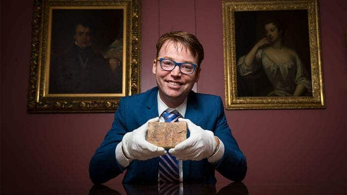 Australian mathematicians Daniel Mansfield pictured holding the the 3700-year-old Babylonian tablet that he claims was used for trigonometry -- it would make it the earliest such instance in history. Credit: UNSW.