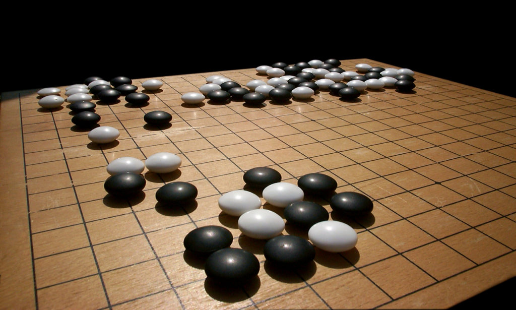 To win at Go, one of two players must surround its opponent by controlling more territory. Credit: Wikimedia Commons.