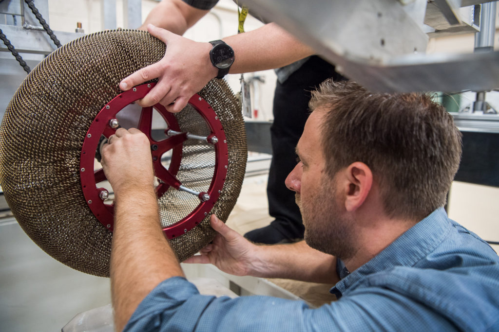 Engineer Colin Creager attaches the latest version of the SMA Spring Tire to a test rig in the SLOPE lab. This version weighs 15 lbs, can carry double the amount of load as the previous version and performs better in the deep space temperatures. Credit: NASA.
