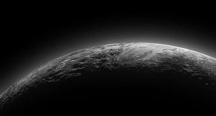 Just 15 minutes after its closest approach to Pluto on July 14, 2015, NASA's New Horizons spacecraft looked back toward the sun and captured a near-sunset view of the rugged, icy mountains and flat ice plains extending to Pluto's horizon. Credit: NASA.