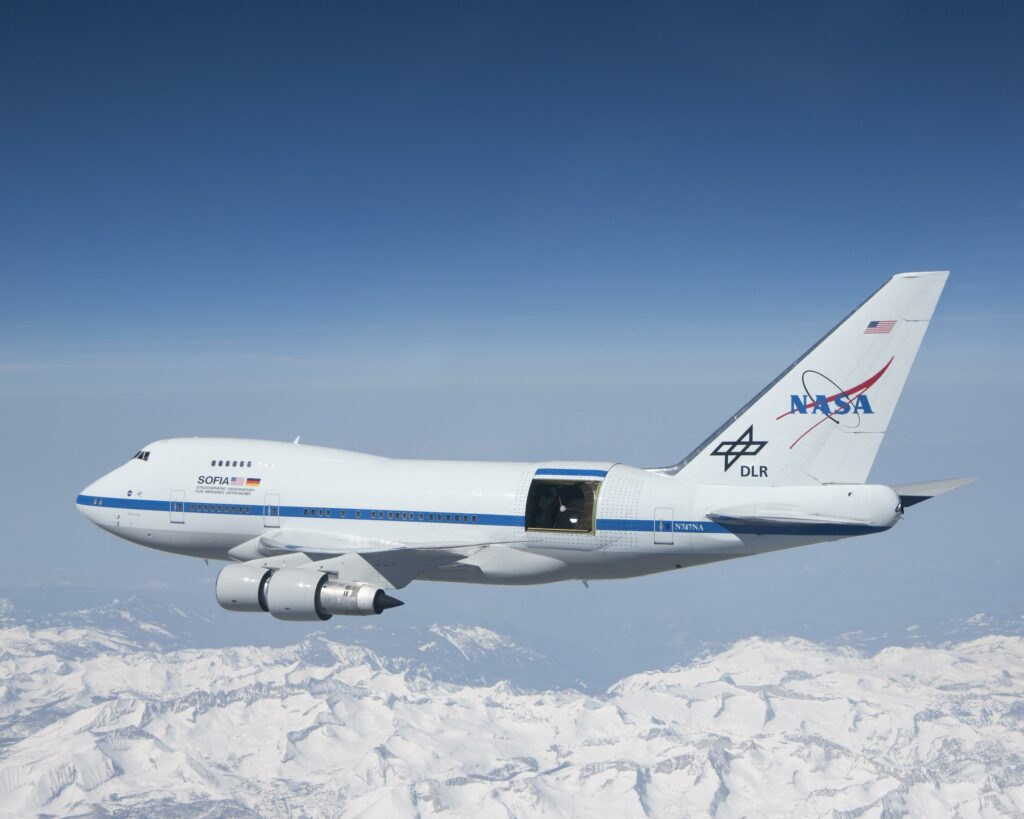 SOFIA-- here seen soaring over the snow-covered Sierra Nevada mountains with its telescope door open during a test flight--has allowed NASA to make a major new moon discovery. SOFIA is a modified Boeing 747SP aircraft. (NASA/Jim Ross)