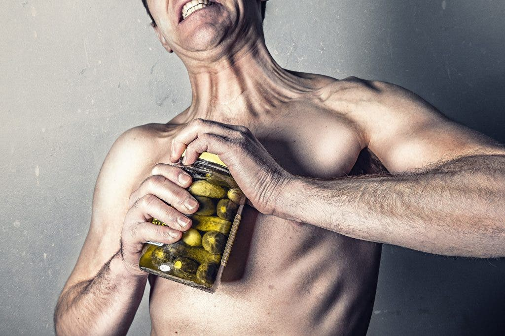 Stock photo of a man trying to exaggeratedly open a jar of pickles.
